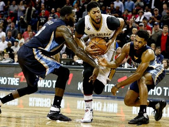 New Orleans Pelicans forward Anthony Davis (23) drives past Memphis Grizzlies forward JaMychal Green (0) and guard Andrew Harrison (5) during a second overtime quarter in a game at the Smoothie King Center. The Grizzlies defeated the Pelicans 110-108 in double overtime.