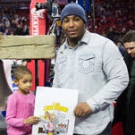 Devon Still and his daughter, Leah Still, courtside before ringing the ceremonial liberty bell at the start of a game between the Philadelphia 76ers and Golden State Warriors at Wells Fargo Center in February.