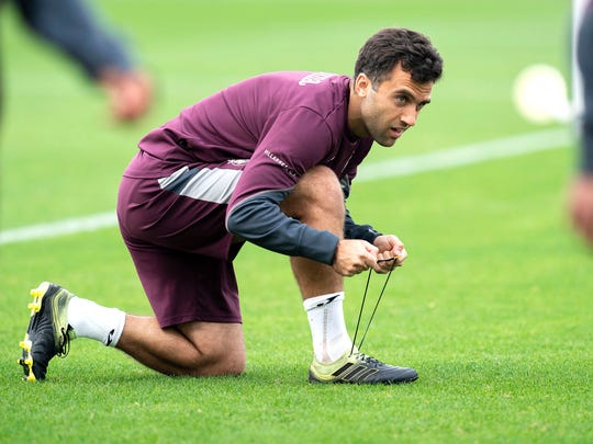 In this photo released by Villarreal Club de Futbol on Tuesday, Oct. 15, 2019, Giuseppe Rossi laces up his sneakers during a training with Spanish club Villarreal, Spain.  The 32-year old Rossi, the American-born striker who played for the Italian national team before a series of injuries slowed his career, is back at Villarreal, the Spanish club where he thrived in his prime. (Villareal F.C via AP)