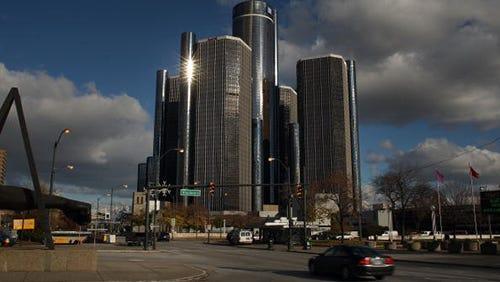 Cars drive past the General Motors headquarters in Detroit, Michigan.
