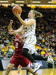 Iowa's Samantha Logic (22) puts up a layup past Indiana's