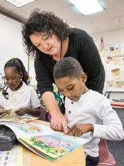 Kindergarden teacher Michelle Andersen helps Malachi