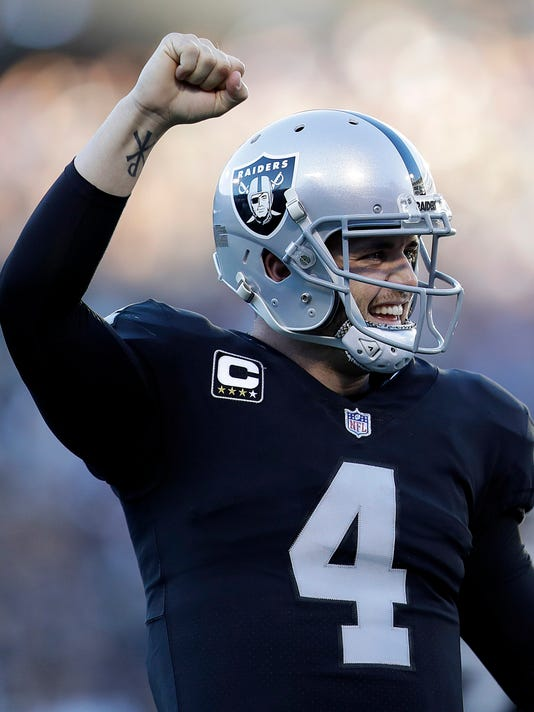 Oakland Raiders quarterback Derek Carr (4) celebrates after running back DeAndre Washington scored a touchdown during the second half of an NFL football game against the New York Giants in Oakland, Calif., Sunday, Dec. 3, 2017. (AP Photo/Marcio Jose Sanchez)