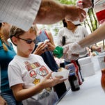 A young child gets sprinkles on his ice cream during the 26th annual Ice Cream Social, benefiting Girls Inc. of Greater Indianapolis, a nonprofit that helps girls ages 6 to 18, along Monument Circle on July 8, 2016.