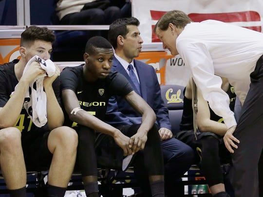 Oregon coach Dana Altman, right, speaks to players