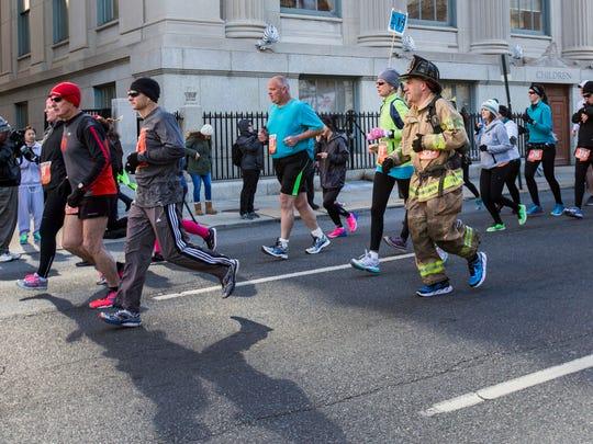 Firefighter Steve Bender runs in full gear in the Caesar Rodney Half-Marathon in Wilmington on Sunday morning.