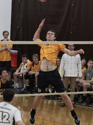 Chris Kiser of Moeller gets way above the net as he sets up to spike the ball from the middle position.