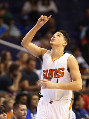 Phoenix Suns guard Devin Booker (1) points up before playing against the Dallas Mavericks during the first quarter at Talking Stick Resort Arena in Phoenix, Ariz. April 9, 2017.