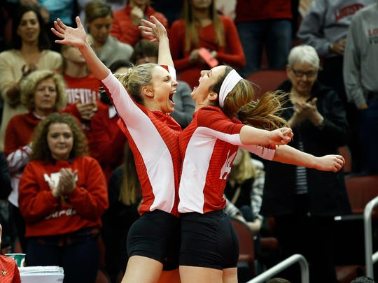 Louisville's Katie George, left, and Roxanne McVey fly high for the chest bump on their senior night. Nov. 22, 2015