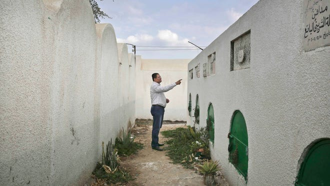 Reda el-Danbouki, Egyptian lawyer for 13-year-old Sohair al-Bata'a, who died undergoing the procedure of female genital mutilation, points at her grave in Dierb Biqtaris village, on the outskirts of Aga town in Dakahliya, 75 miles northeast of Cairo, Egypt, on Nov. 5, 2014.