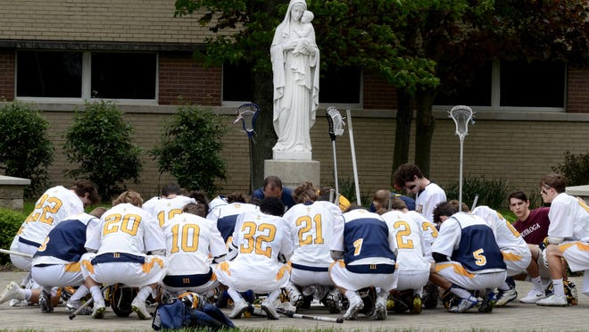 As they do before each game, the Moeller lacrosse team prays at the statue of Mary in the courtyard.