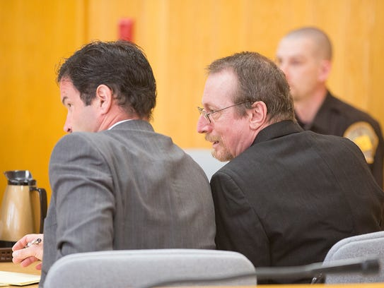 Joseph Reinwand, 56, right, talks to his defense attorney,