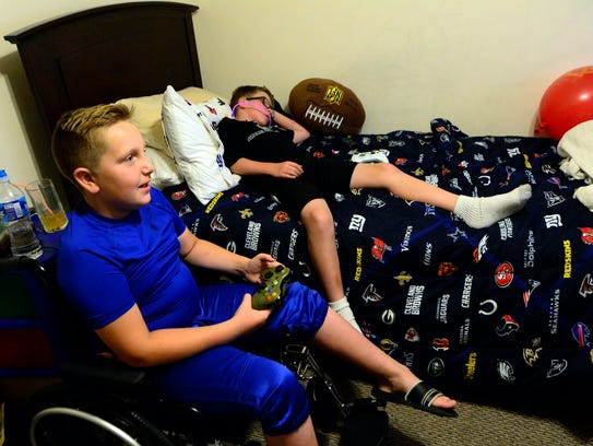 Long time friend Harley Nelson, 9, left, plays video