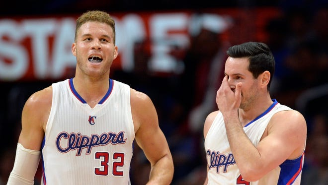 Los Angeles Clippers guard J.J. Reddick wipes his face after being fouled while Los Angeles Clippers forward Blake Griffin reacts against the Memphis Grizzlies at Staples Center.