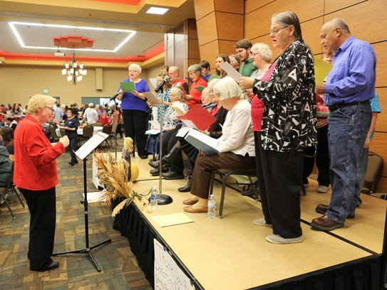 Marie Schumacher, left, leads members of the Trinity Lutheran Church choir during a performance at the Salvation Army Thanksgiving meal on Thursday at the Farmington Civic Center.