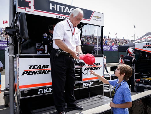 Roger Penske, owner of Team Penske, center, signs his