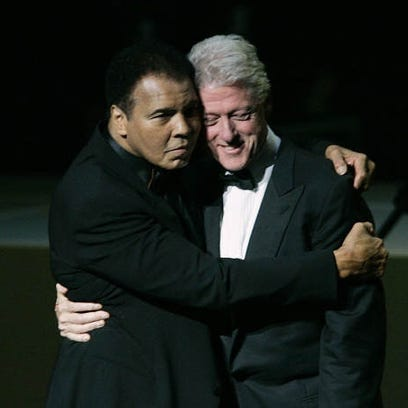 With his wife Lonnie looking on, Muhammad Ali hugs former President Bill Clinton as he walks on stage at the grand opening gala celebration for the Muhammad Ali Center Saturday, Nov. 19, 2005.