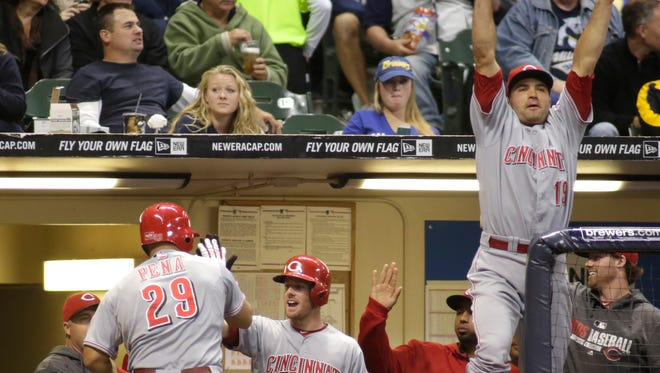 Cincinnati Reds' Joey Votto right, reacts after Brayan Pena, left, scored on a bases-loaded walk by Milwaukee Brewers pitcher Yovani Gallardo during the fourth inning.