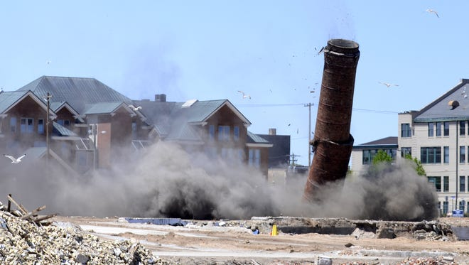 Hamilton Manufacturing Co.'s 233-foot smokestack crumbles to the ground as part of a scheduled demolition May 31, 2015, in Two Rivers.