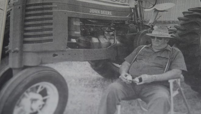 Fred Williamson of Sturgis relaxed next to this 1942 A-model John Deere tractor at the Union County Fair in July 1997. Mike Cowan of Sturgis was the owner.