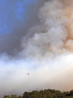 A Cal Fire helicopter flies through smoke in this file photo.
