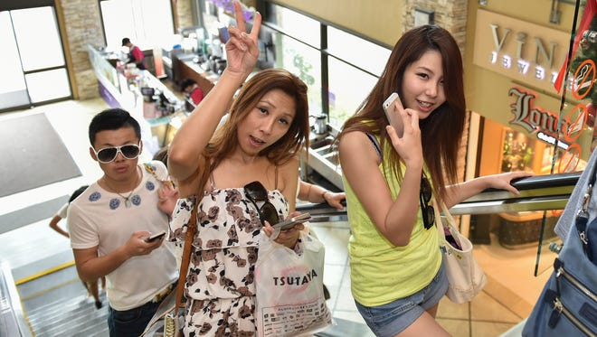 Guam tourists pose for the camera while riding a JP Super Store escalator in Tumon on Jan. 4.