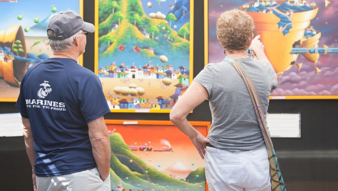 Bob and Ruth Waldheim, of Naples, admire Edwin Guerrero's artwork during the Naples Artcrafters Fine Art and Craft Show at Cambier Park in Naples on Saturday, Feb.y 13, 2016.