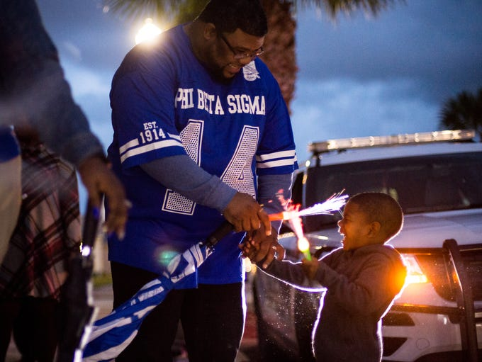 Bryce Jackson (right), 3, of Fort Pierce, shares a