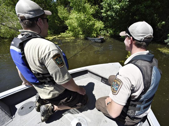 Stearns County Water Patrol Officers Ethan Reinert and Koleby Dingmann tow an old partially submerged boat out of the weeds on Horseshoe Lake near Richmond.