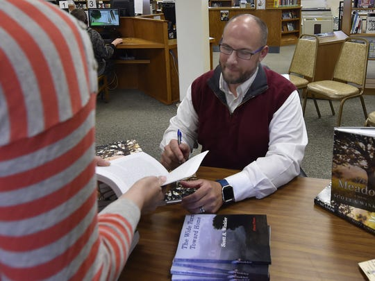 """Luxemburg-Casco teacher and author Scott A. Winkler signs copies of his new book """"The Meadow'' on May 19 at the Algoma Public Library."""