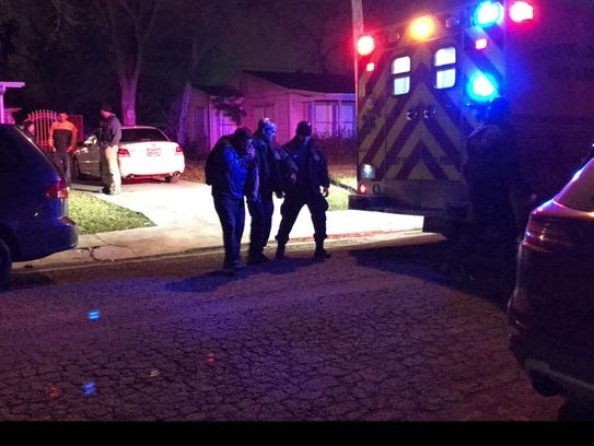 Medics and officers escort a man to an ambulance. A