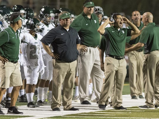 Dinuba's Kevin Scharton, in black, is the head coach of the Emperors' football team.