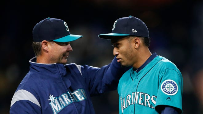 Mariners manager Scott Servais (left) congratulates closer Edwin Diaz after getting a save Friday night against Texas.