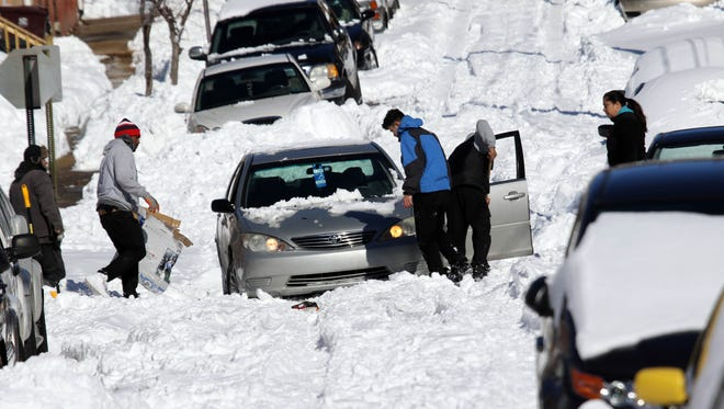Residents try to free a car stuck on Delamore Place near Fourt Street in Wilmington on Sunday afternoon.