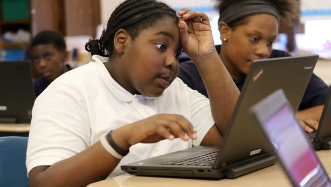 12 year-old Sabrina Dickens, a fifth grader at Elbert-Palmer Elementary School, works on math problems alongside 12 year-old classmate Donnica Price.
