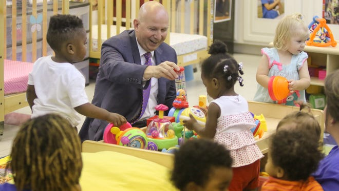 Gov. Jack Markell plays with children in an infant class at Parents and Children Together at Tech United Cerebral Palsy of Delaware child care center at Sussex Technical High School on Wednesday morning while visiting the school to see how a federal grant has helped early childhood learning.