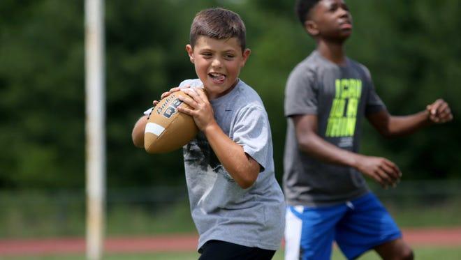 9 year-old Brady McBride prepares to through a football during drills  at Tatnall School football camp on Thursday.