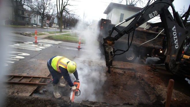 Construction workers search for a water pipeline on Kalamazoo Avenue in Kalamazoo, Mich.