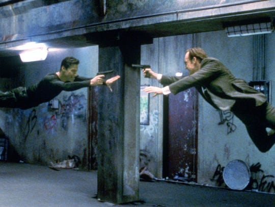 "Neo (Keanu Reeves, left) and Agent Smith (Hugo Weaving) face off in ""The Matrix."""