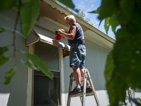 Gene Devore paints the soffit of a home at 3511 6th