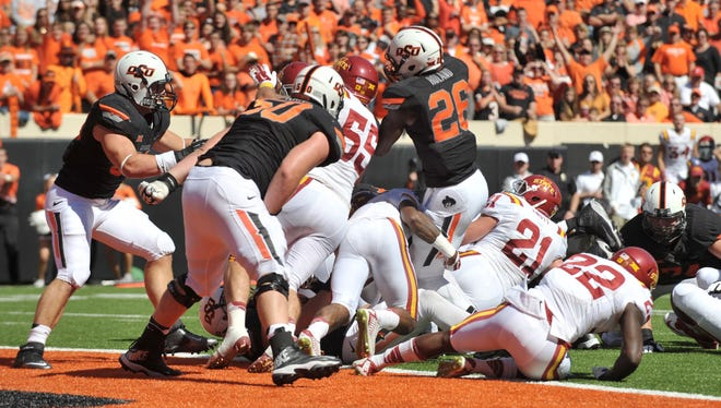 Desmond Roland (26) scores a controversial touchdown on the final play of the first half against Iowa State as Jevohn Miller (55) defends.