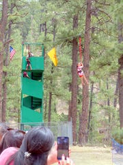 A mother snaps a shot of her daughter as she slides down the midtown Ruidoso zipline.