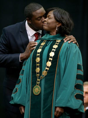 FAMU's 11th president Elmira Mangum gets a kiss from her son Joshua Daniel after he hooded her during her installation as president on Friday.