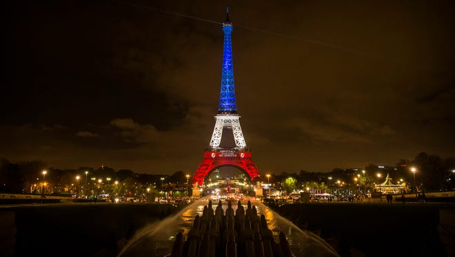The Eiffel Tower is illuminated in the colors of the French flag in tribute for the victims of the 13 November terror attacks, in Paris on Monday.