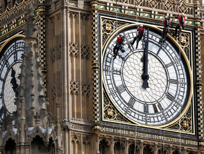 Workers hang outside the clock face as they clean the Big Ben clocktower of the Houses of Parliament in London, Monday, Aug. 18, 2014.