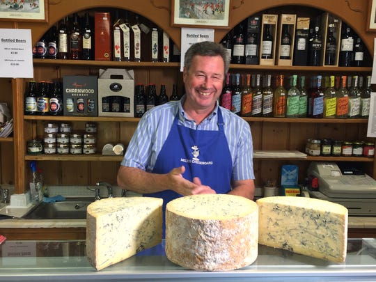 Tim Brown, the owner of the the Melton Cheeseboard, weighs out some cheese in his shop in Melton Mowbray, England.