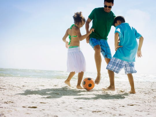 Kids Playing Soccer with Dad on the Beach