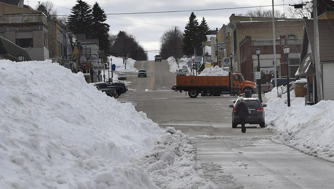 A Kewaunee County Highway Department truck hauls away snow by the truckload from downtown on Tuesday. The National Weather Service reported 18.5 inches of snow falling on the city during last weekend's blizzard.