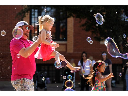Clay Collier holds up his daughter, Collyns, 4, in the bubbles during the Children's Art & Literacy Festival on Saturday, June 10, 2017, in downtown Abilene.