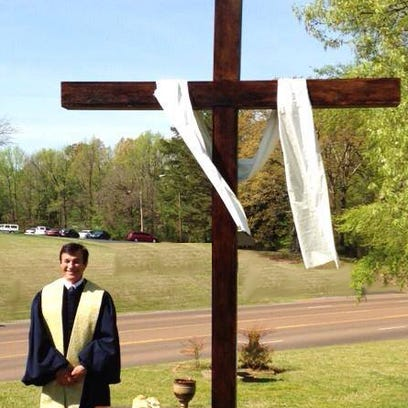 Pastor Barry Matthews stands by the outdoor cross on